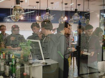 Zdjęcie przedstawia wnętrze kuchni DaftCode, gdzie grupka ludzi pije drinki