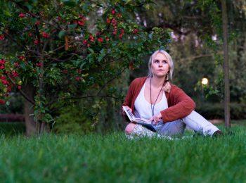 Zamyślona autorka siedząca na trawie z otwartym notesem